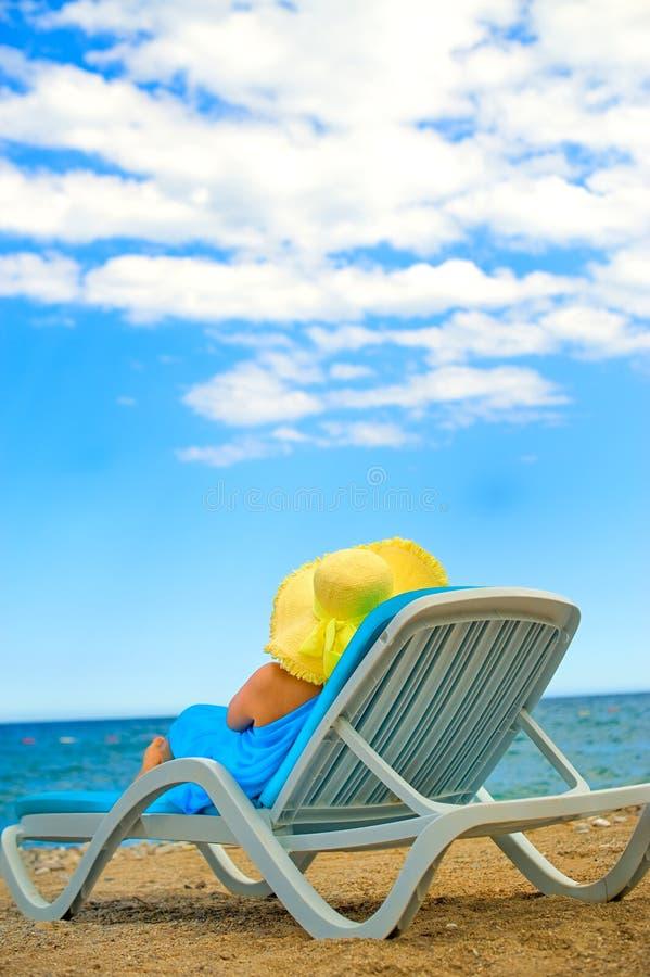 A mulher nova senta-se na sala de estar do chaise fotografia de stock royalty free