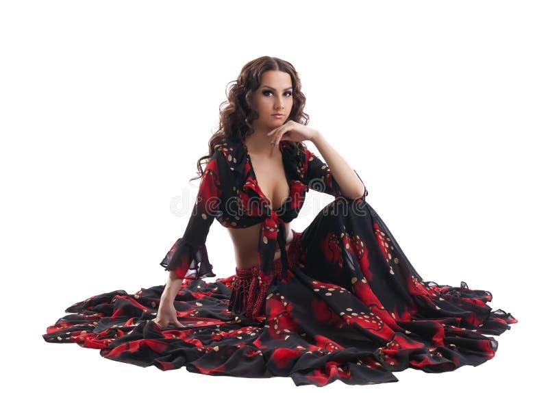 A mulher nova senta-se no traje preto e vermelho aciganado foto de stock