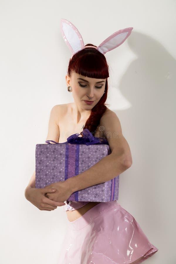 Mulher nova 'sexy' do ruivo em um terno do coelho com presentes imagens de stock