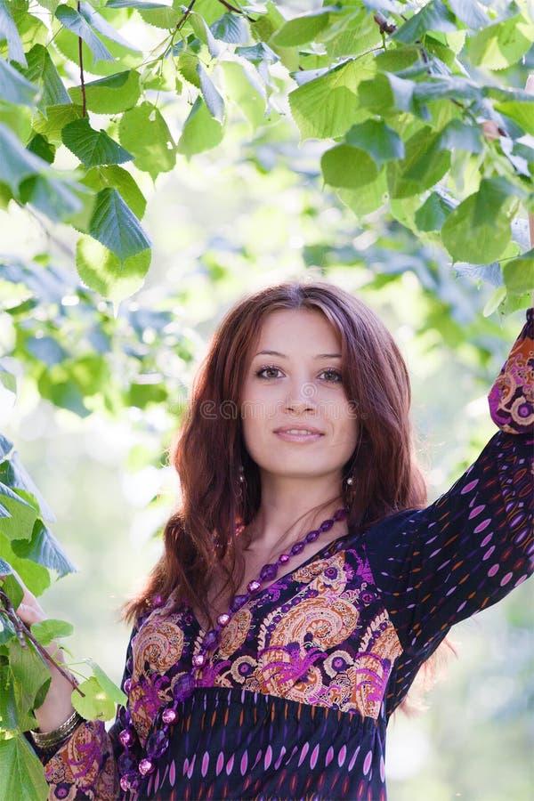 Mulher nova sob a árvore verde no parque da mola fotografia de stock royalty free
