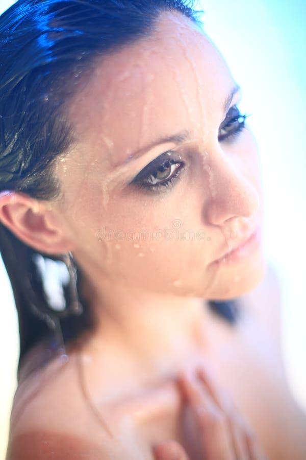 Mulher nova sob o pulverizador do chuveiro fotografia de stock royalty free