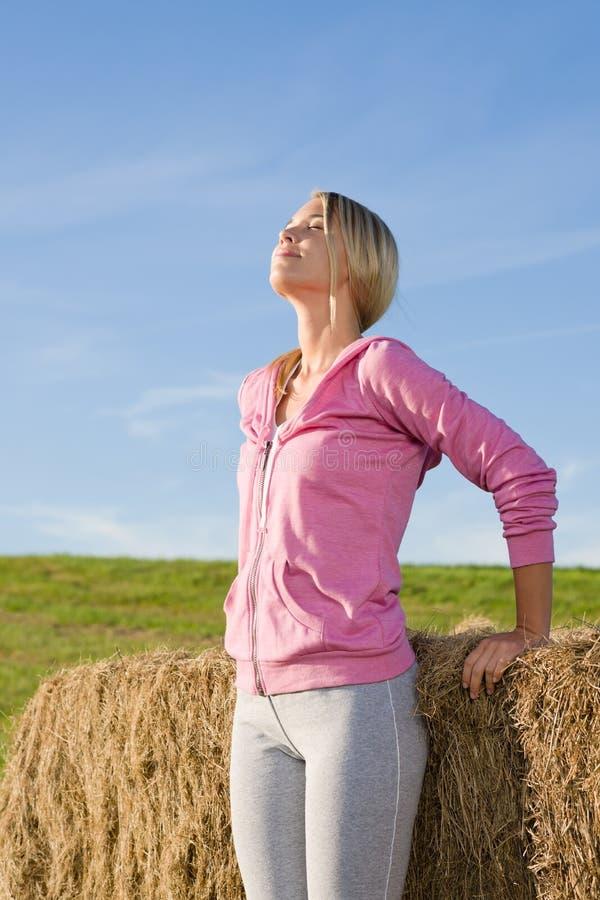 A mulher nova Sportive relaxa pelo por do sol das balas foto de stock royalty free