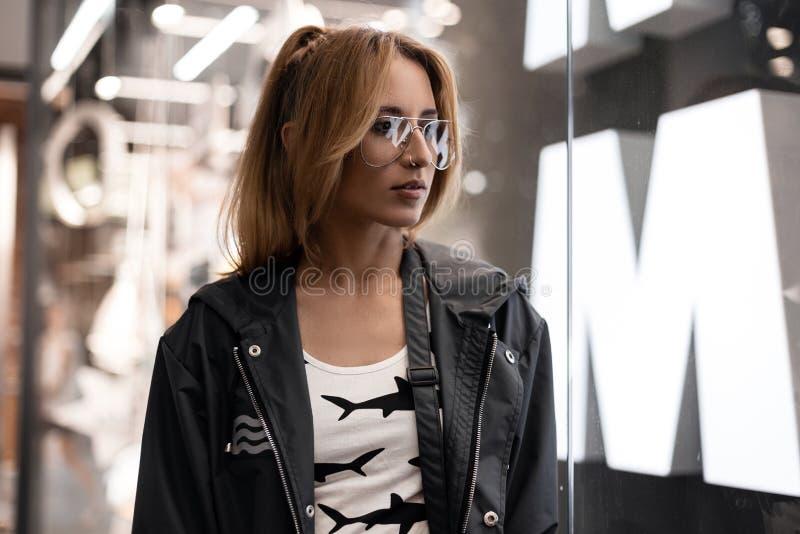 Mulher nova urbana do moderno em vidros do vintage no t-shirt branco na moda com um teste padrão em uma posição à moda do revesti fotografia de stock royalty free