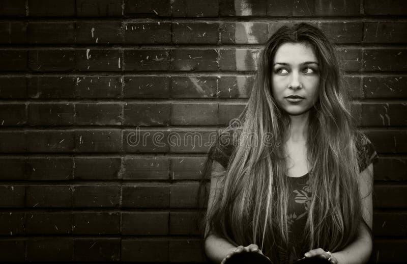 Mulher nova urbana que senta-se perto da parede de tijolo fotografia de stock royalty free