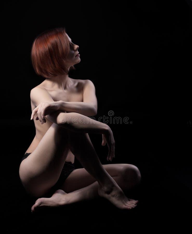 A mulher nu da beleza senta-se no preto fotos de stock