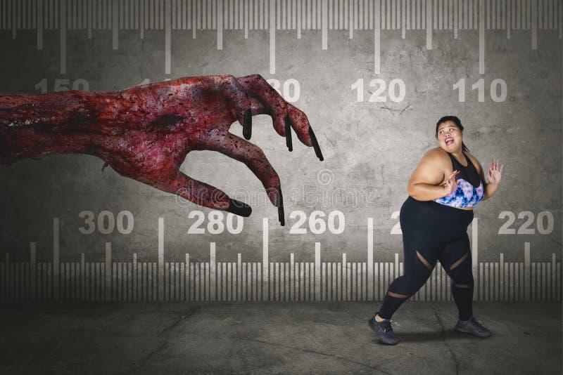 A mulher obeso assustado corre longe da mão assustador foto de stock royalty free