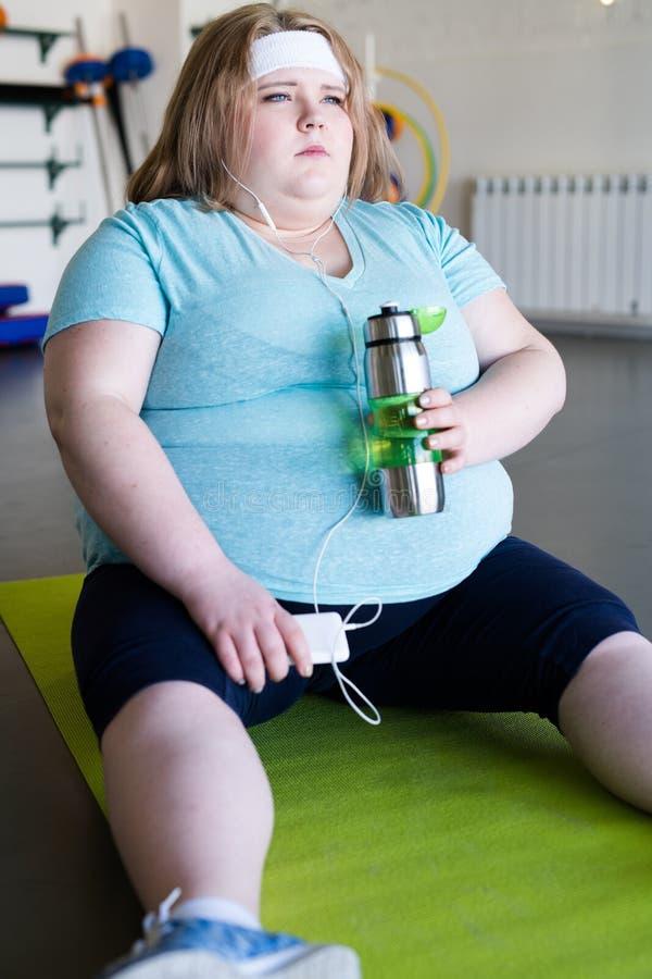 Mulher obeso cansado que senta-se na esteira fotos de stock royalty free