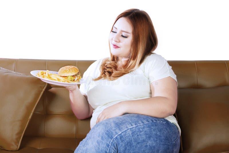 Mulher obeso com comida lixo no sofá imagens de stock