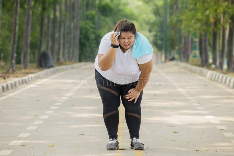A mulher obeso parece cansado após a corrida foto de stock