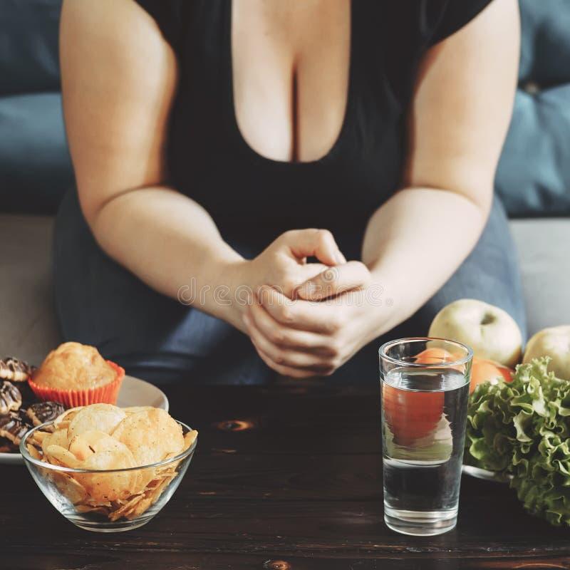 Mulher obeso que escolhe entre doces e vegetais fotografia de stock