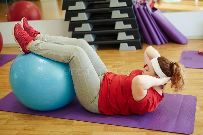 Mulher obeso que faz Sit Ups Using Fitness Ball no Gym imagem de stock