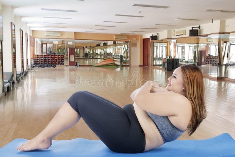 Mulher obeso que faz triturações na esteira foto de stock