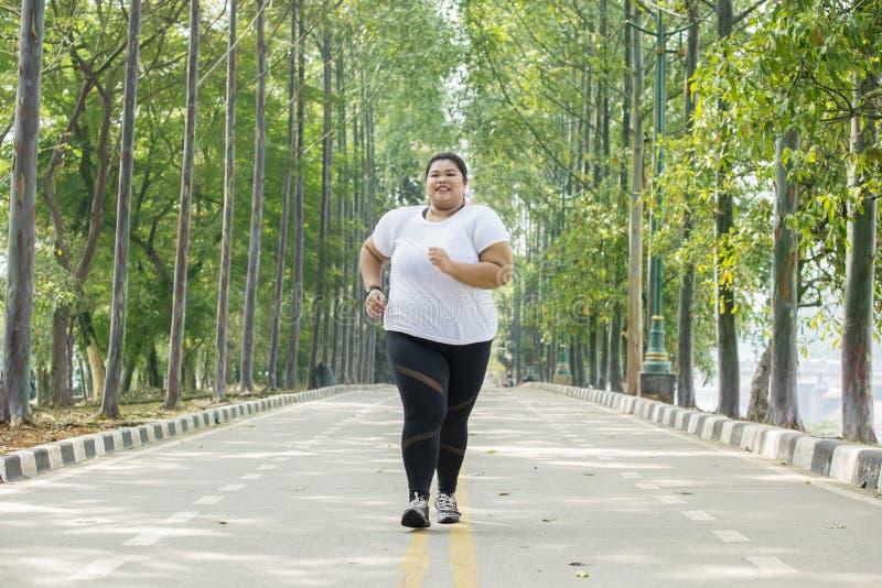 Mulher obeso que movimenta-se na estrada imagens de stock royalty free