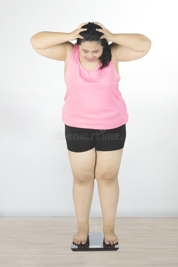 Mulher obeso que olha a escala do peso fotos de stock royalty free
