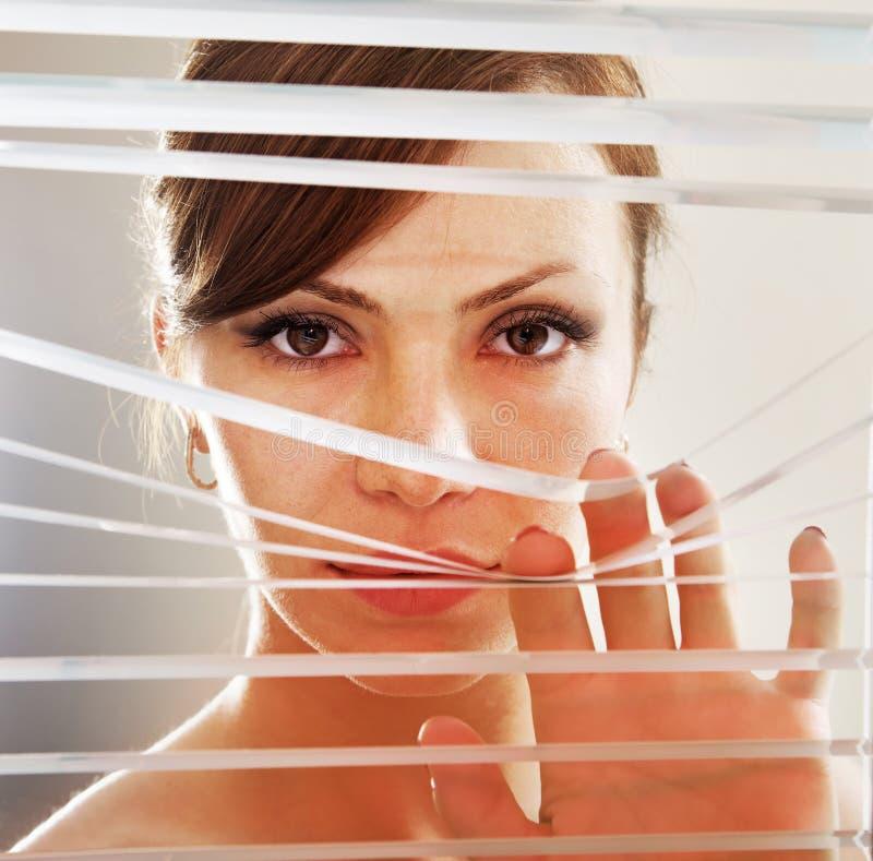 A mulher observa através das cortinas foto de stock royalty free