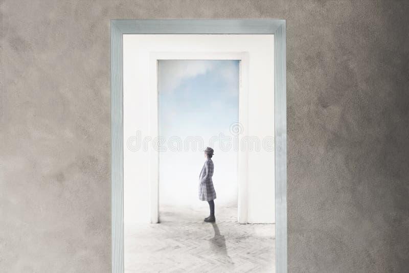 A mulher observa curioso a porta que abre para a liberdade e os sonhos imagens de stock royalty free