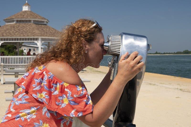 Mulher observando com binocular a fichas fotografia de stock royalty free