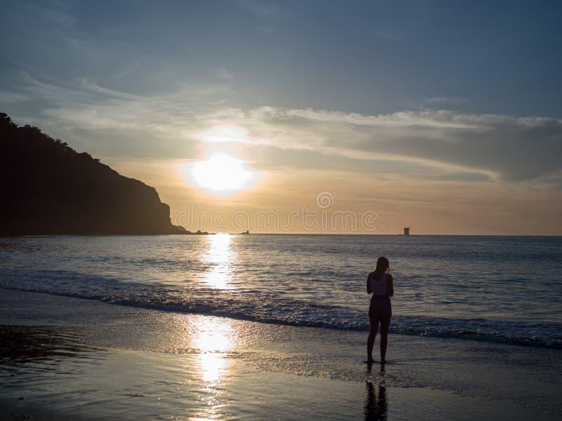 Mulher observando o sol de ajuste sobre o Oceano Pacífico fotografia de stock
