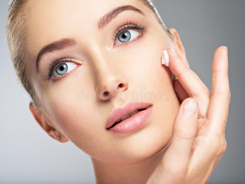 A mulher obtém o creme na cara Conceito do cuidado de pele fotos de stock