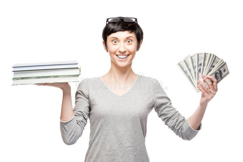 Mulher ocasional alegre que guardara livros e dinheiro fotos de stock royalty free