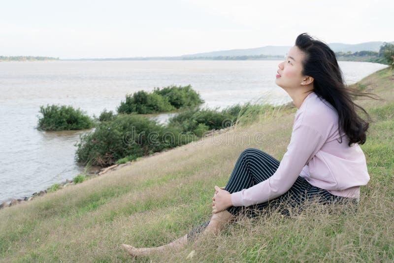 Mulher OCASIONAL asiática que senta-se em uma pastagem que levanta em um fundo da opinião de céu azul do beira-rio Retrato da jov fotos de stock