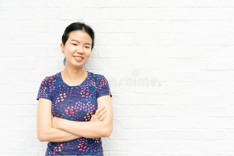 A mulher ocasional bonita asiática nova e cruzou seus braços indique o espaço vazio no fundo branco da parede de tijolo Mulher fe fotos de stock royalty free