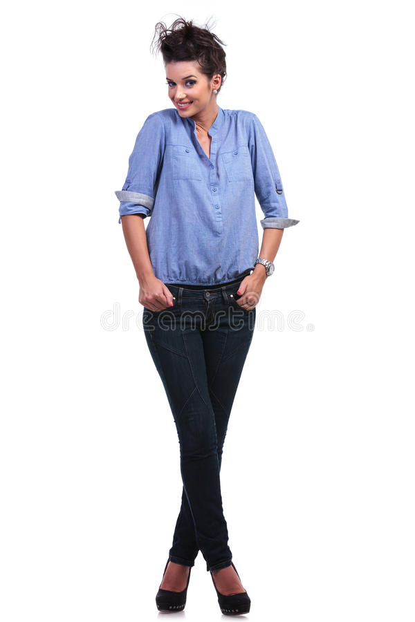 Mulher ocasional com mãos em uns bolsos e nos pés cruzados imagem de stock
