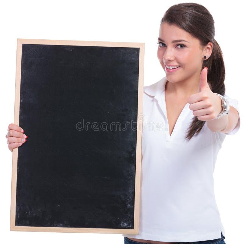 Mulher ocasional com quadro-negro & aprovação fotografia de stock royalty free