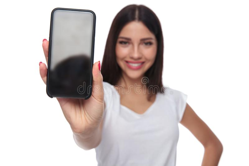 A mulher ocasional no t-shirt branco mostra a tela do telefone celular fotografia de stock