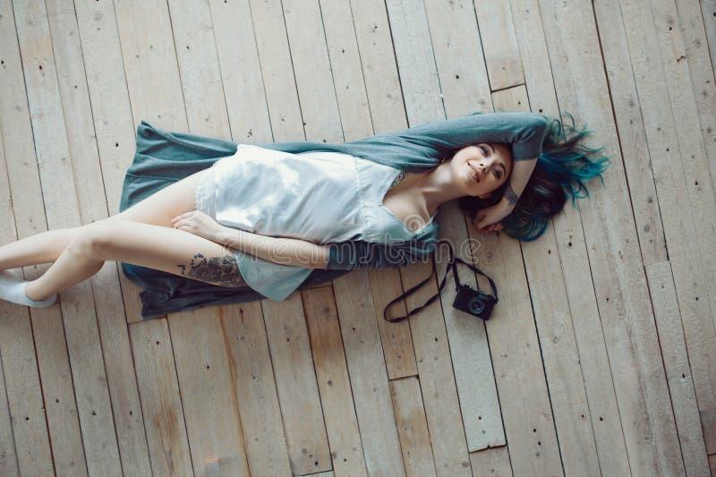 Mulher ocasional nova despreocupada bonita que encontra-se no assoalho de madeira foto de stock