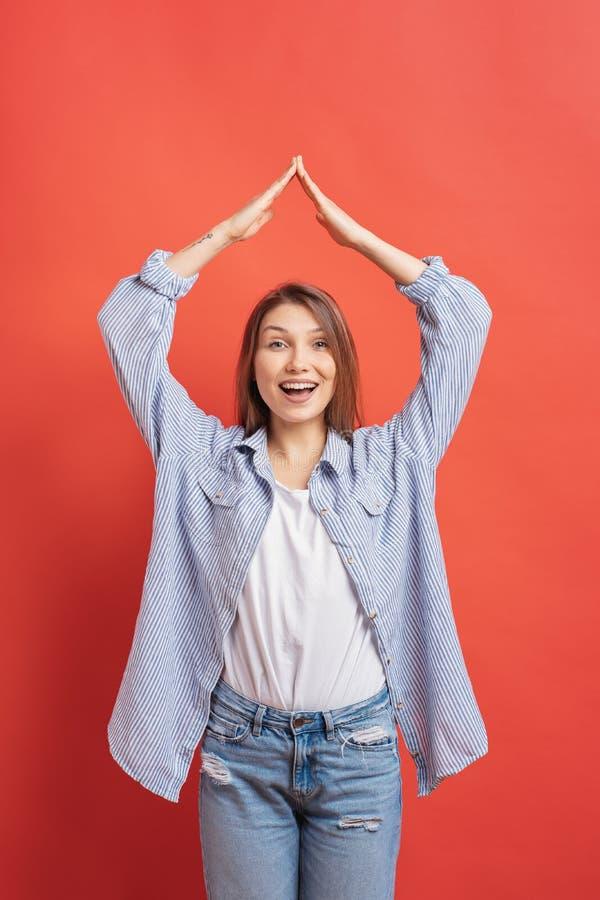 Mulher ocasional nova que guarda as mãos em cima como o sinal da casa sobre um fundo vermelho fotografia de stock
