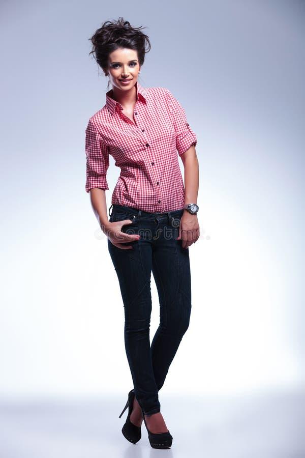 Mulher ocasional nova 'sexy' que está com suas mãos em uns bolsos imagem de stock