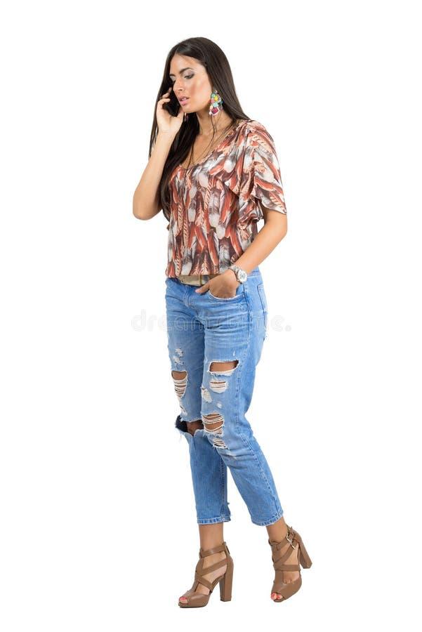 Mulher ocasional ocupada nova que fala no telefone celular ao andar fotos de stock