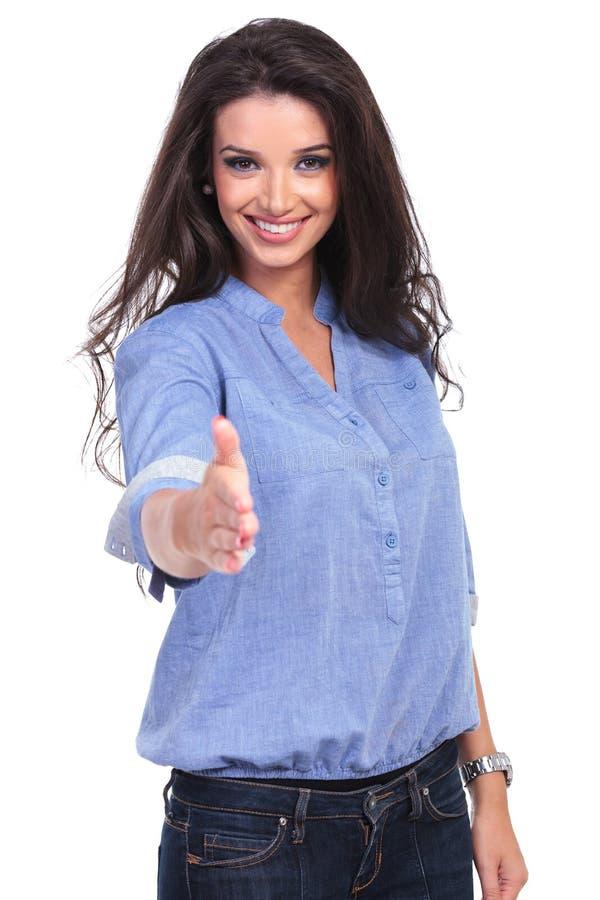 A mulher ocasional oferece um aperto de mão foto de stock