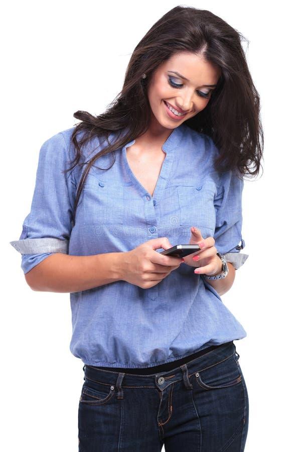 A mulher ocasional olha seu telefone foto de stock royalty free