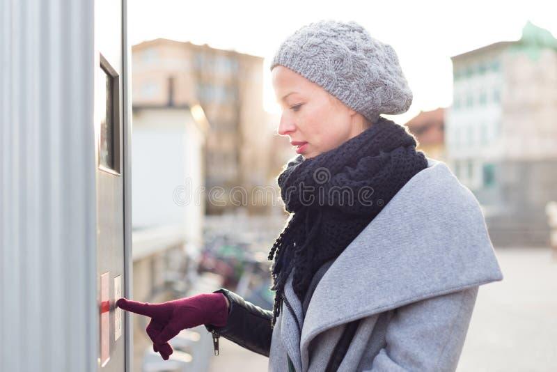 Mulher ocasional que compra bilhetes do transporte público na máquina vedning urbana da cidade no dia de inverno frio imagens de stock royalty free