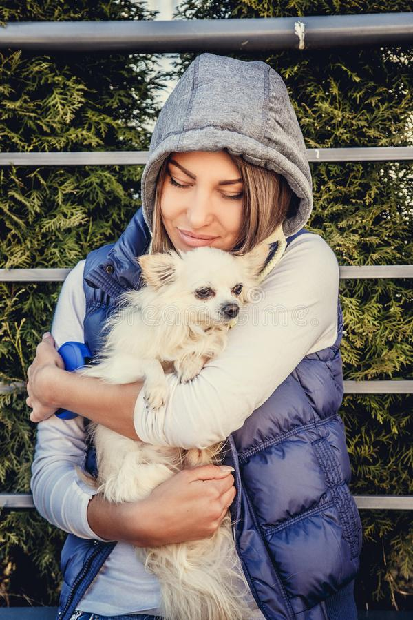 Mulher ocasional que guarda o cão branco pequeno fotos de stock royalty free