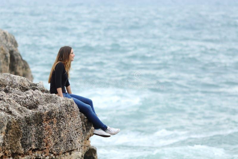 Mulher ocasional que senta-se em um penhasco que olha o mar imagem de stock