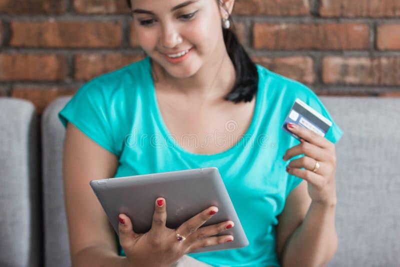 Mulher ocasional que usa a tabuleta em casa imagem de stock
