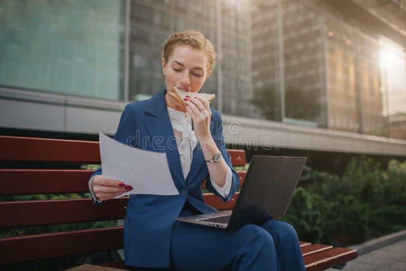 A mulher ocupada é com pressa, ela não tem o tempo, ela está indo comer fora o petisco Trabalhador que come e que trabalha com imagens de stock royalty free
