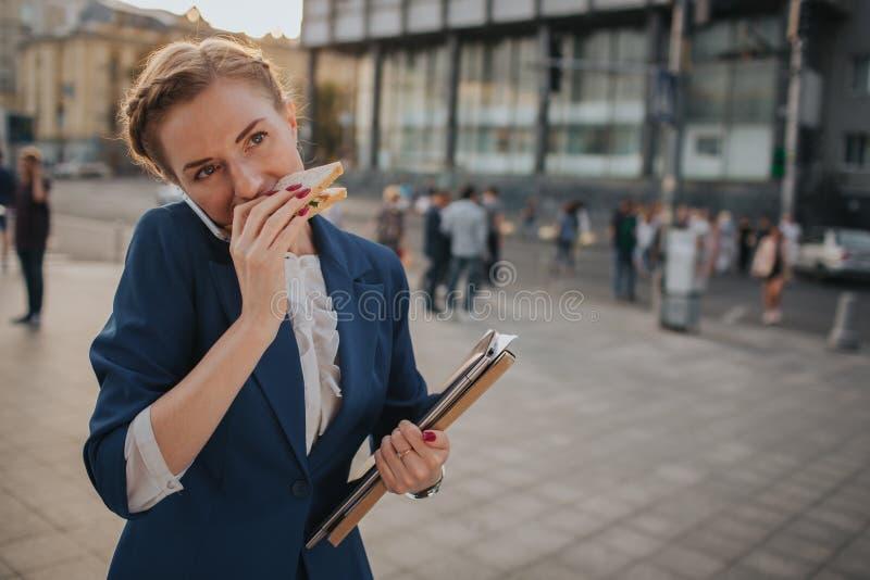 A mulher ocupada é com pressa, ela não tem o tempo, ela está indo comer o petisco ir Trabalhador que come, café bebendo foto de stock royalty free