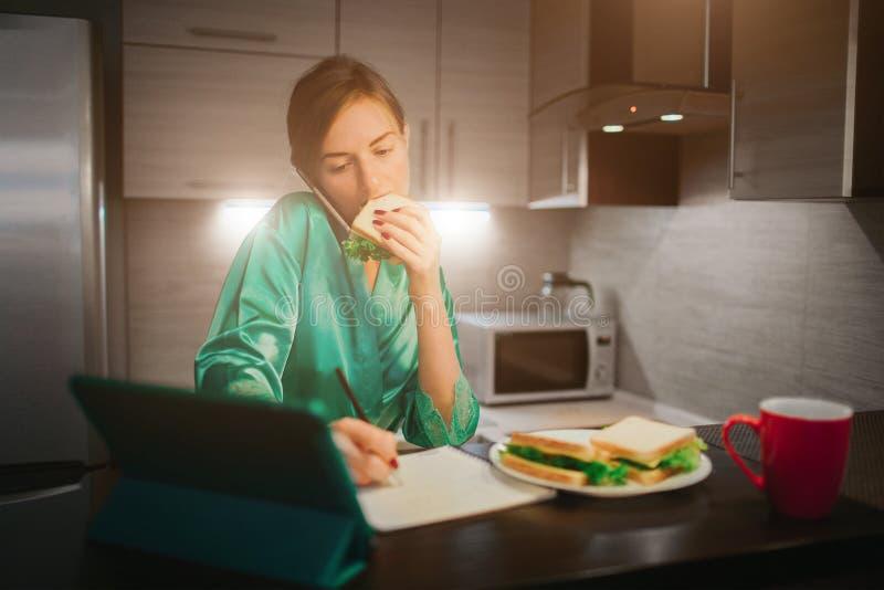 Mulher ocupada que come, café bebendo, falando no telefone, trabalhando em um portátil ao mesmo tempo Fazer da mulher de negócios fotos de stock