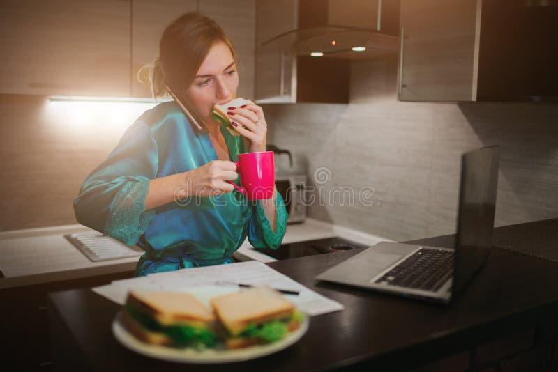 Mulher ocupada que come, café bebendo, falando no telefone, trabalhando em um portátil ao mesmo tempo Fazer da mulher de negócios imagem de stock