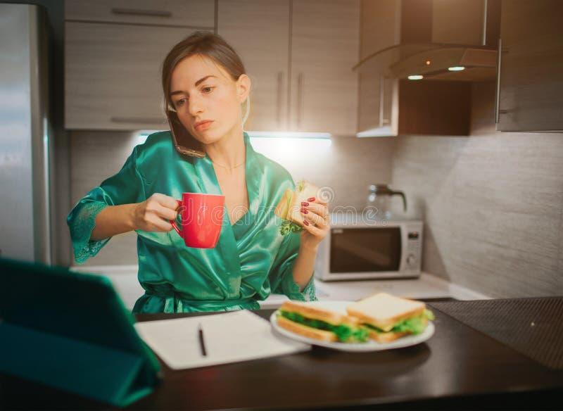 Mulher ocupada que come, café bebendo, falando no telefone, trabalhando em um portátil ao mesmo tempo Fazer da mulher de negócios imagens de stock royalty free
