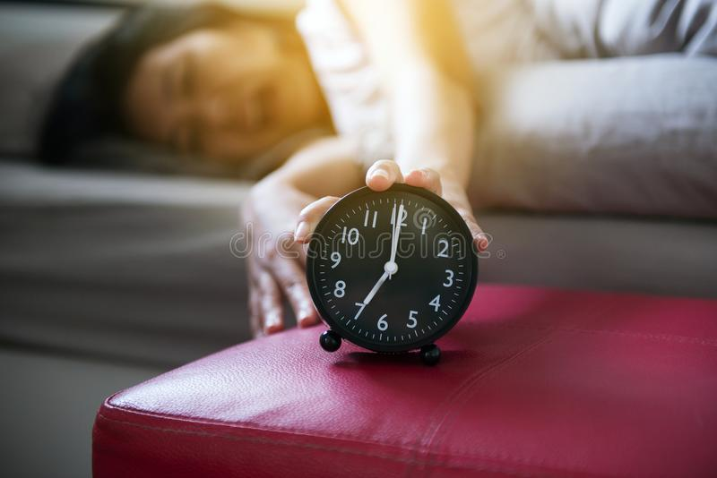 A mulher odeia obter forçada acordando o amanhecer, fêmea que estica sua mão ao alarme de soada para desligar o despertador imagens de stock