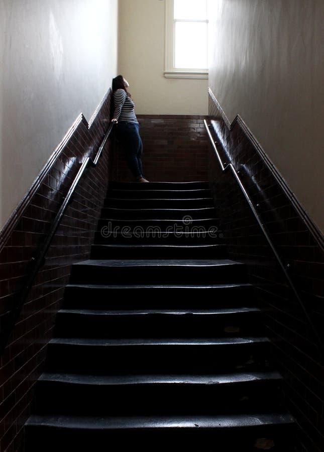 A mulher olha acima na luz da janela alta na parte superior do vão das escadas escuro da casa do século XIX velha da escola em In fotos de stock royalty free