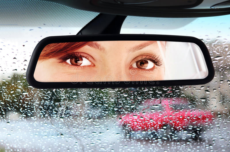 A mulher olha ao espelho retrovisor fotos de stock