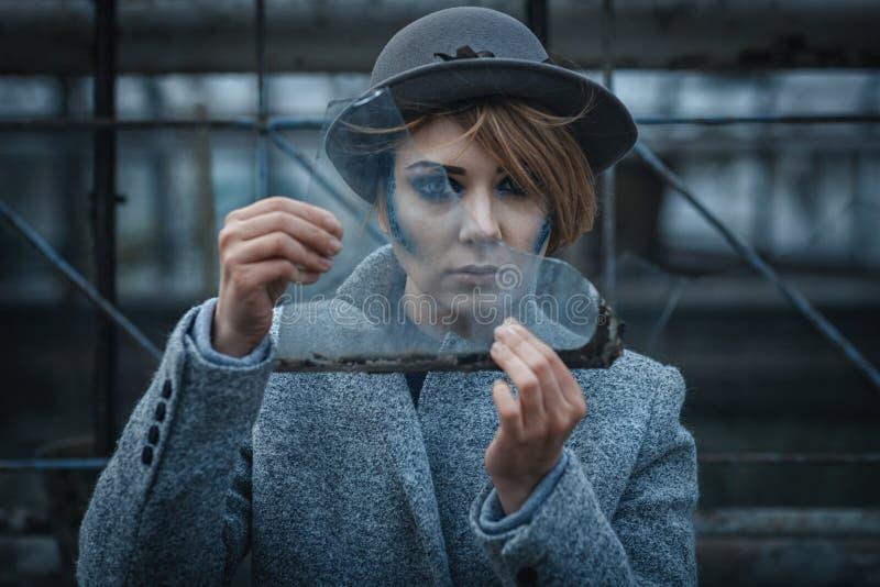 A mulher olha através de vidro afiado quebrado fotos de stock royalty free