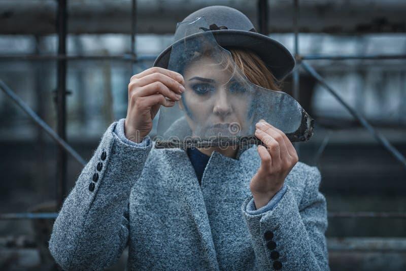 A mulher olha através de vidro quebrado foto de stock royalty free
