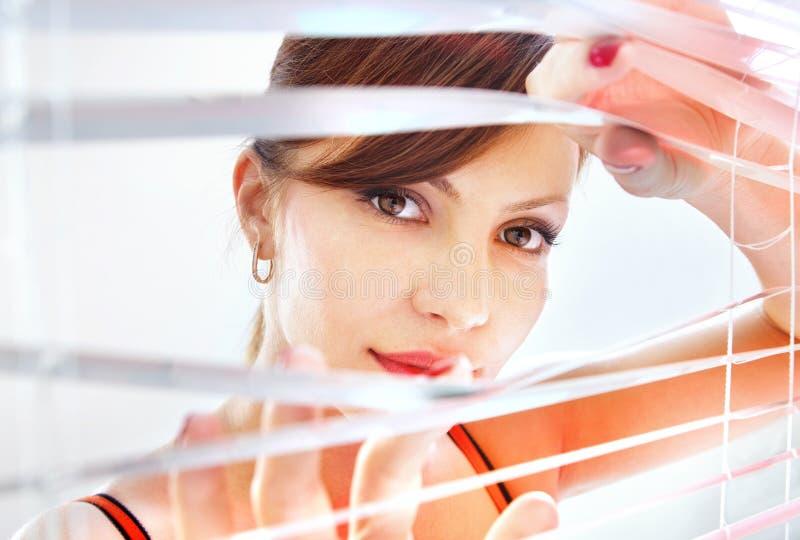 A mulher olha através do jalousie imagem de stock royalty free